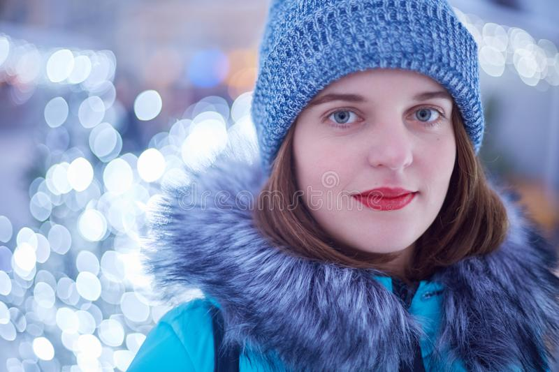 Portrait of beautiful woman with red painted lips, dressed in winter clothes, spends free time outside, stands against sparkles, l royalty free stock photo
