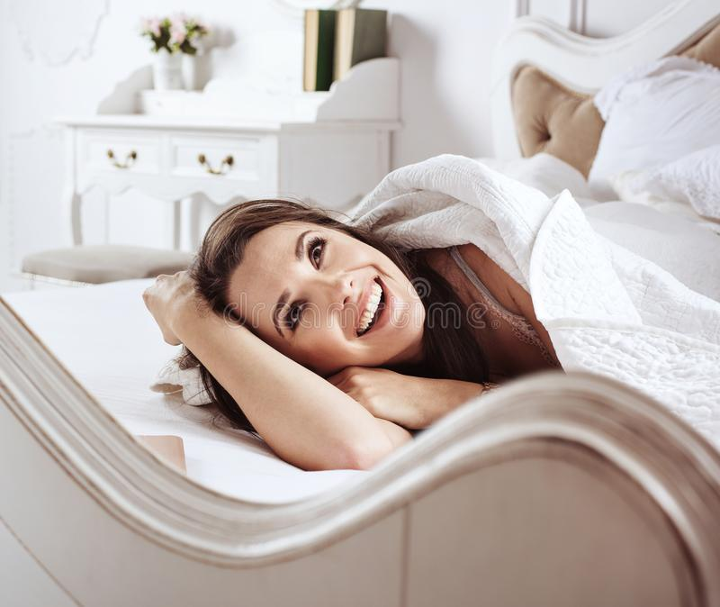 Portrait of a beautiful woman relaxing in bed stock image