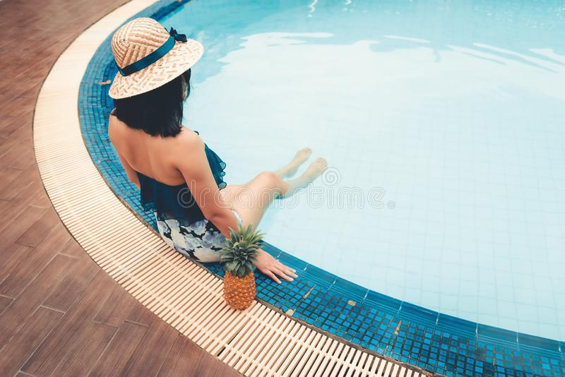 Portrait of beautiful woman relaxing in swimming pool, Recreation sport outdoor and summer vacation., Pretty woman in swimsuit. With her hat relaxing sunbathing royalty free stock photography