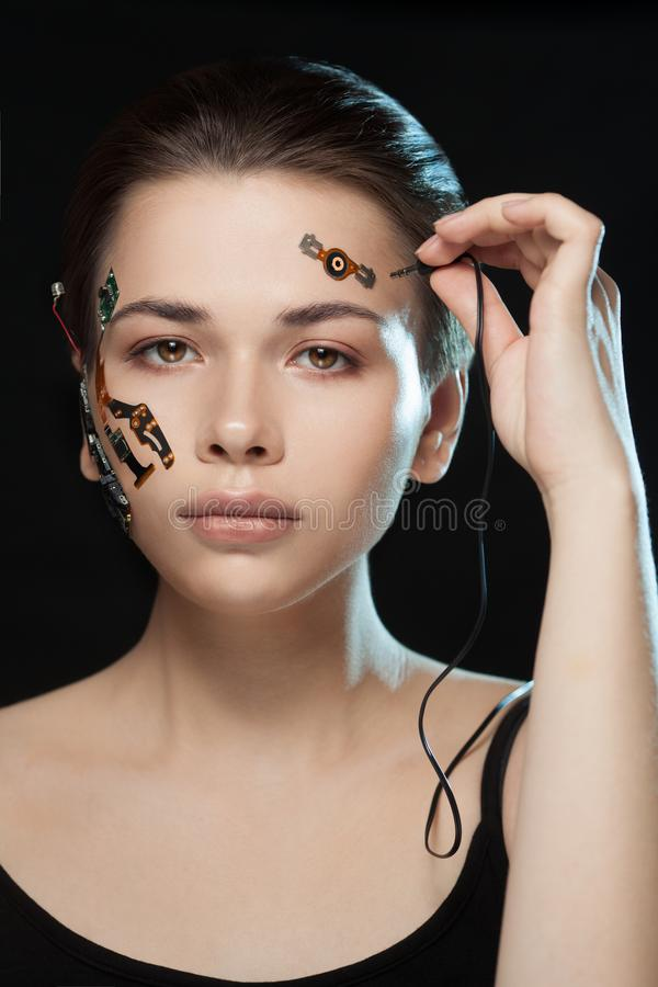 Portrait of a beautiful woman`s face with half human face and half face robot. Portrait of a beautiful cyber woman`s face with half human face and half face royalty free stock images