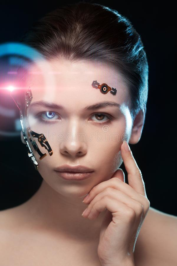 Portrait of a beautiful woman`s face with half human face and half face robot. Portrait of a beautiful cyber woman`s face with half human face and half face stock photography