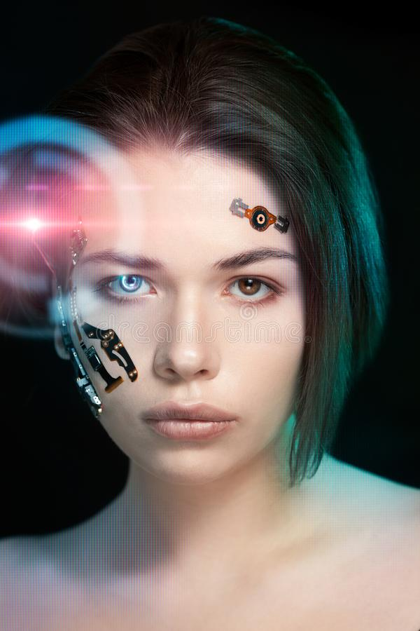 Portrait of a beautiful woman`s face with half human face and half face robot. royalty free stock photography