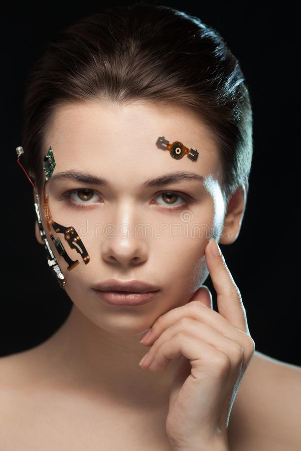Portrait of a beautiful woman`s face with half human face and half face robot. Portrait of a beautiful cyber woman`s face with half human face and half face royalty free stock photos