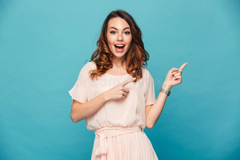 Portrait of beautiful woman 20s wearing adorable dress expressing happiness while pointing fingers aside on copyspace, isolated o stock photography