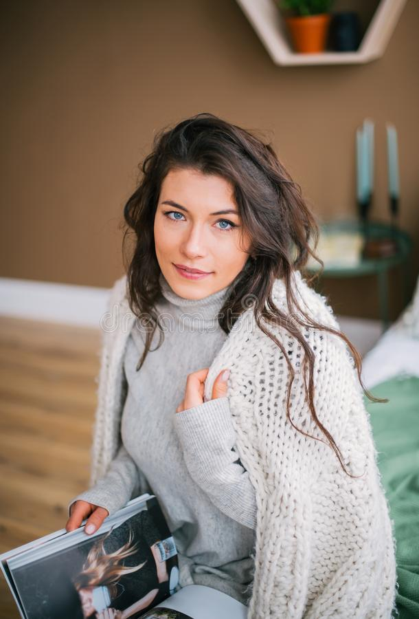 Portrait of beautiful woman in scarf reads the fashionable magazine stock image
