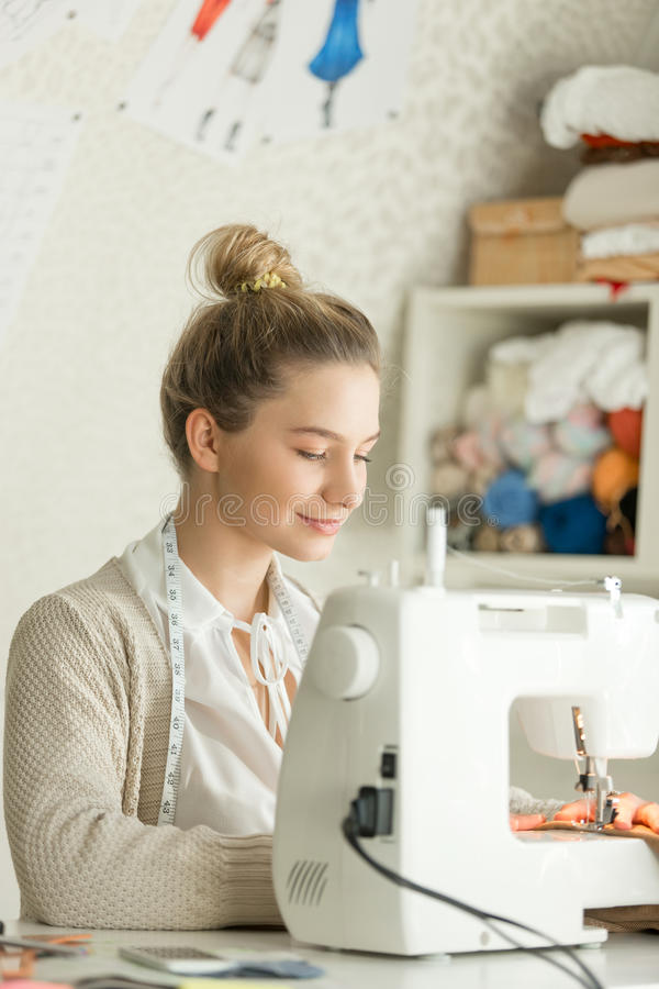 Portrait of a beautiful woman at sewing machine stock photo