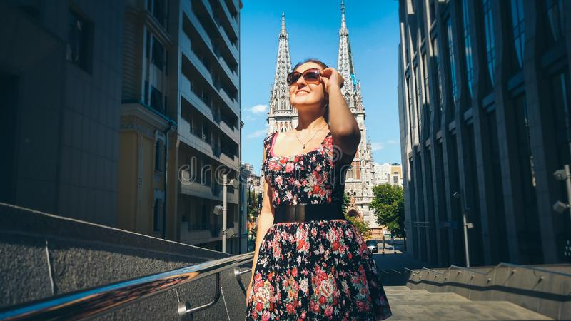 Portrait of beautiful young woman sightseeing old european town with ancient cathedral royalty free stock photography
