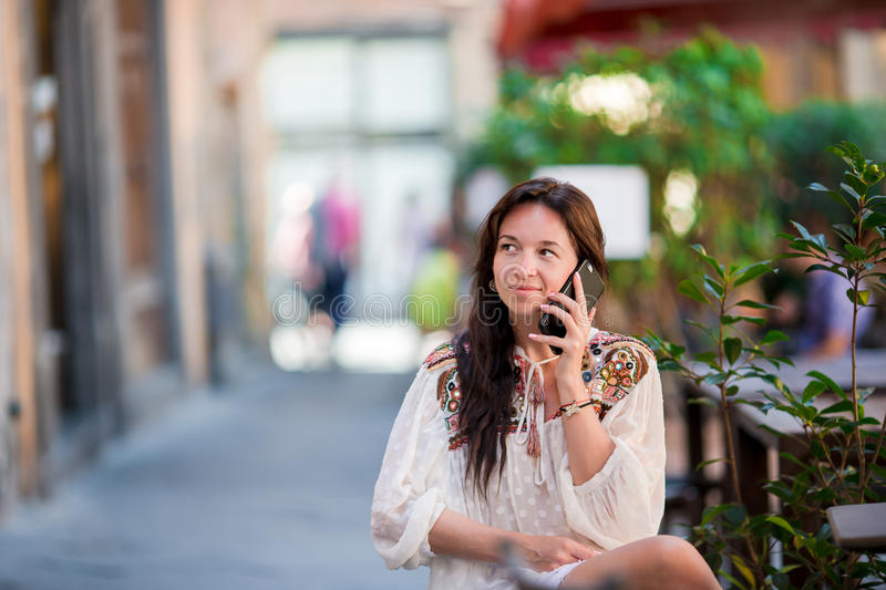 Portrait of beautiful woman sitting in outdoor cafe drinking coffee and talking by smartphone. Portrait of beautiful woman sitting in outdoor cafe drinking royalty free stock image