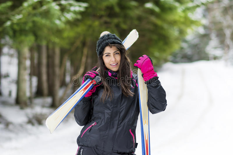Portrait of beautiful woman with ski and ski suit in winter mountain. Portrait of beautiful equipped Brunette woman skier with ski in winter mountain stock photo