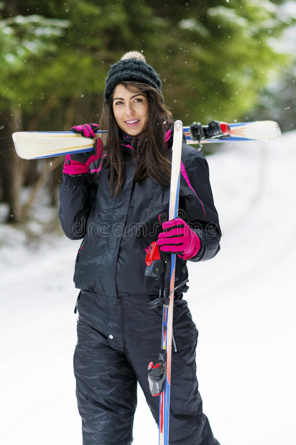 Portrait of beautiful woman with ski and ski suit in winter mountain. Portrait of beautiful equipped Brunette woman skier with ski in winter mountain royalty free stock photography