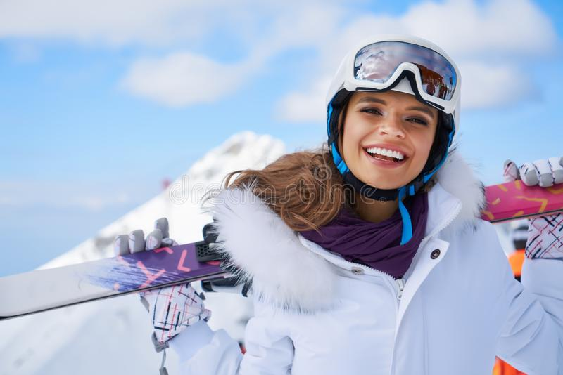 Portrait of beautiful woman with ski and ski suit in winter mountain stock photography