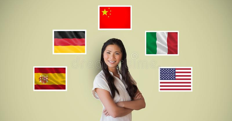 Portrait of beautiful woman smiling with arms crossed standing by flags stock images