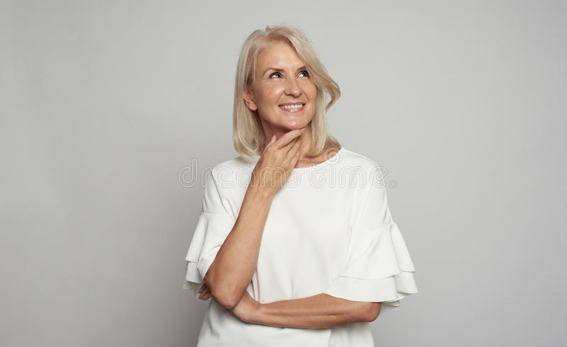 Portrait of a beautiful 50 years woman is smiling, looking up royalty free stock photos