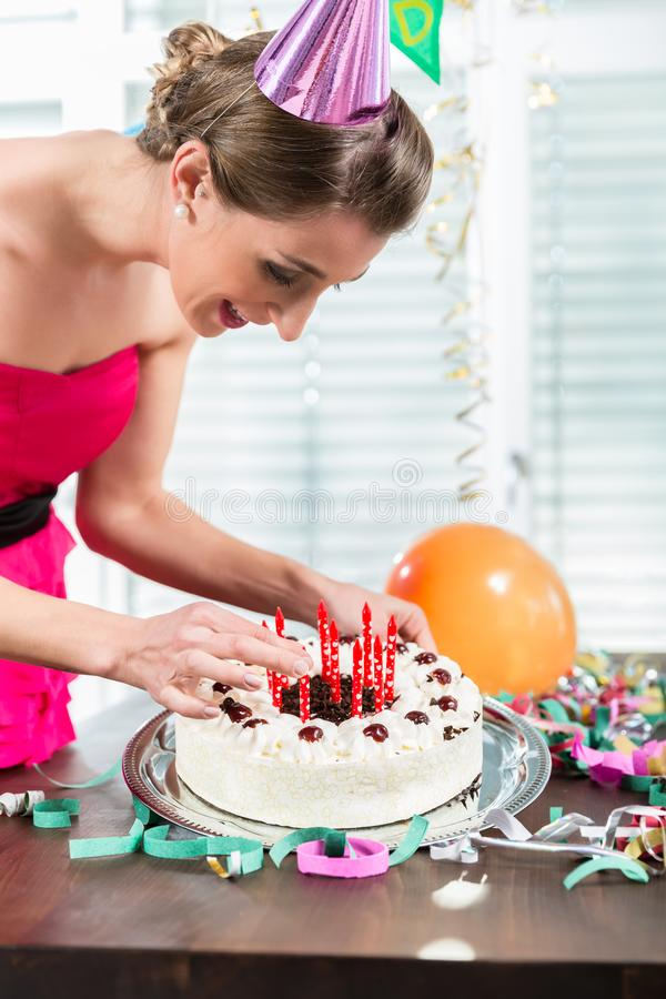 Portrait of a beautiful woman smiling while putting red candles on a cake stock photo