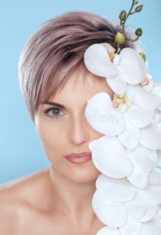 Portrait of a beautiful woman in a spa salon with white orchid in her hand on a blue background. royalty free stock photography