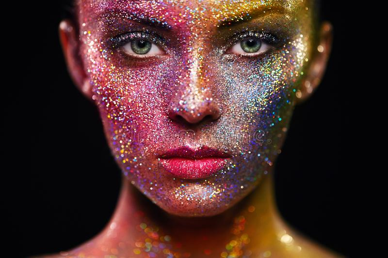 Portrait of beautiful woman with sparkles on her face. Girl with Art Make-Up in Color Light. Fashion Model with Colorful Makeup stock photos