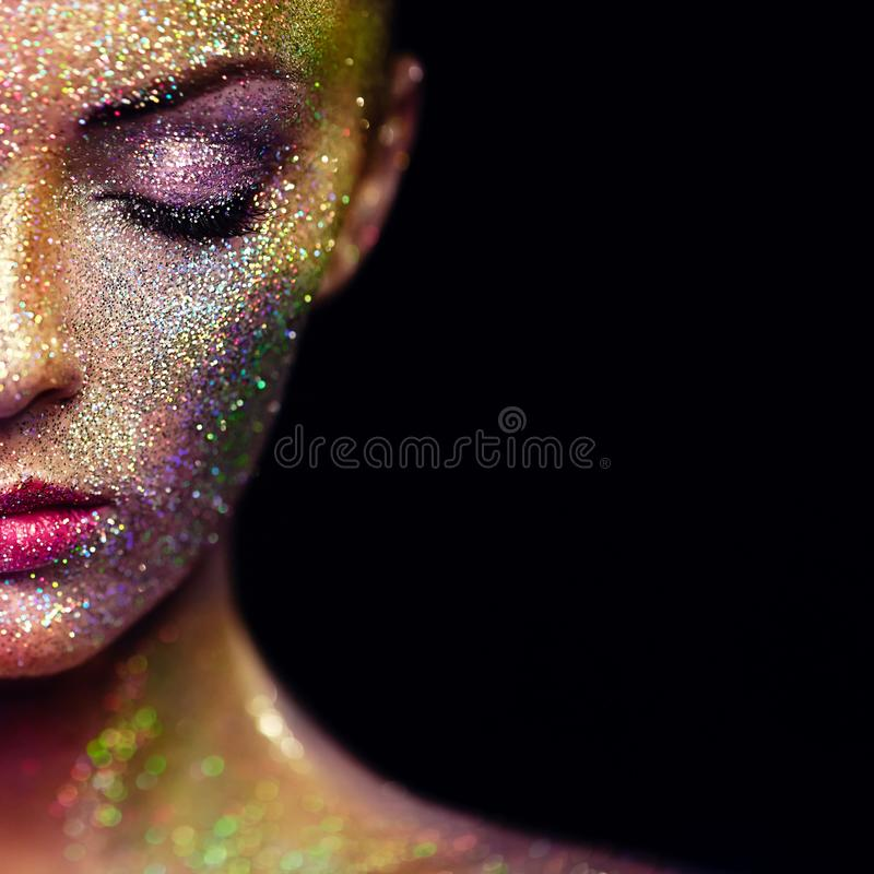Portrait of beautiful woman with sparkles on her face. Girl with Art Make-Up in Color Light. Fashion Model with Colorful Makeup stock photography
