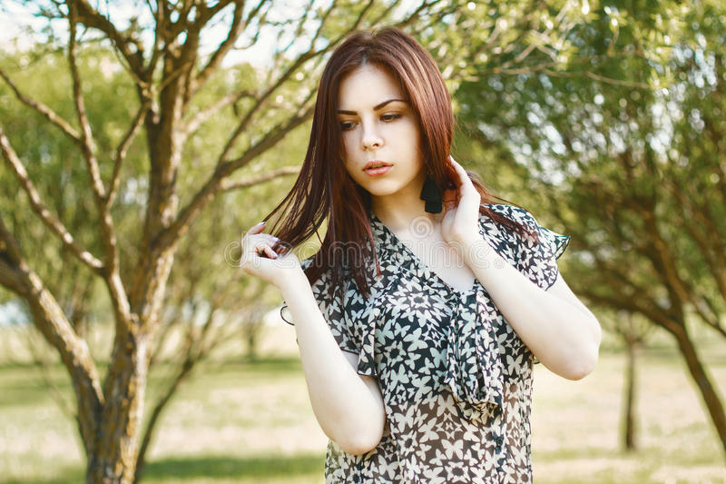 Portrait of a beautiful woman in spring park with small trees. stock image