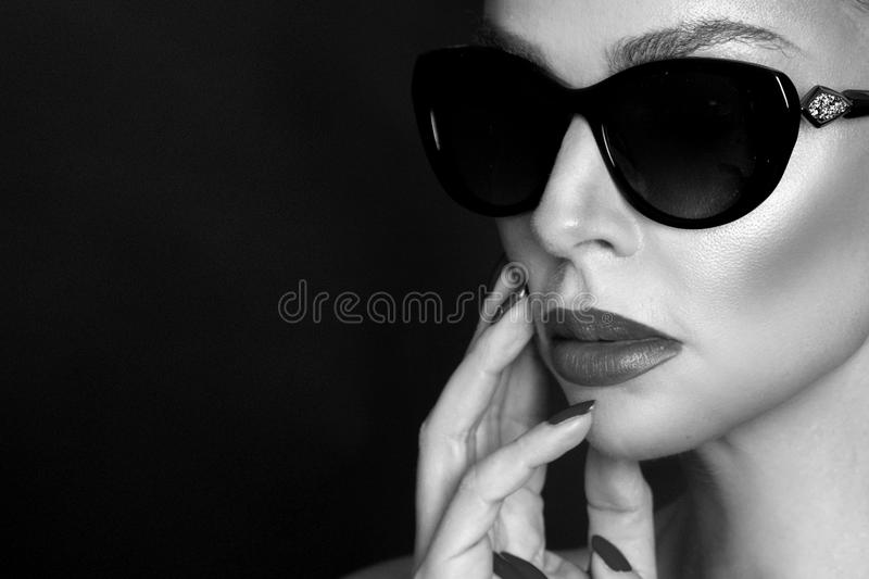 Portrait of beautiful woman with stunning face with flower in hair and in elegant sunglasses, on black background royalty free stock photos