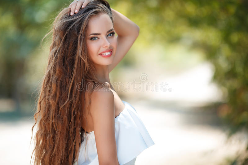 Portrait of beautiful woman in summer Park. Summer portrait, of beautiful woman with grey eyes,long wavy hair,brown hair,light makeup and pink lipstick,nice royalty free stock photos