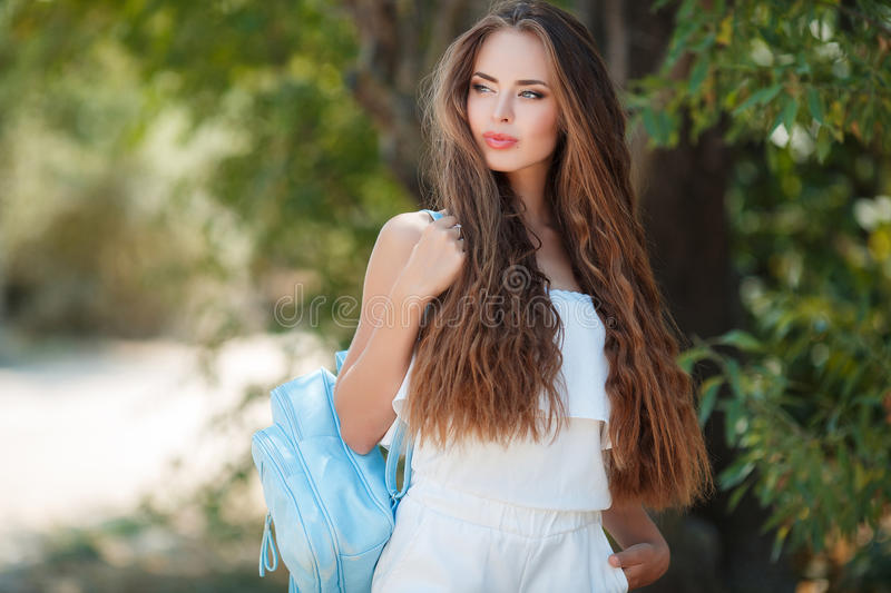 Portrait of beautiful woman in summer Park. Young beautiful brunette woman with long wavy hair and gray eyes,light makeup,pink lipstick dressed in a white blouse stock photos