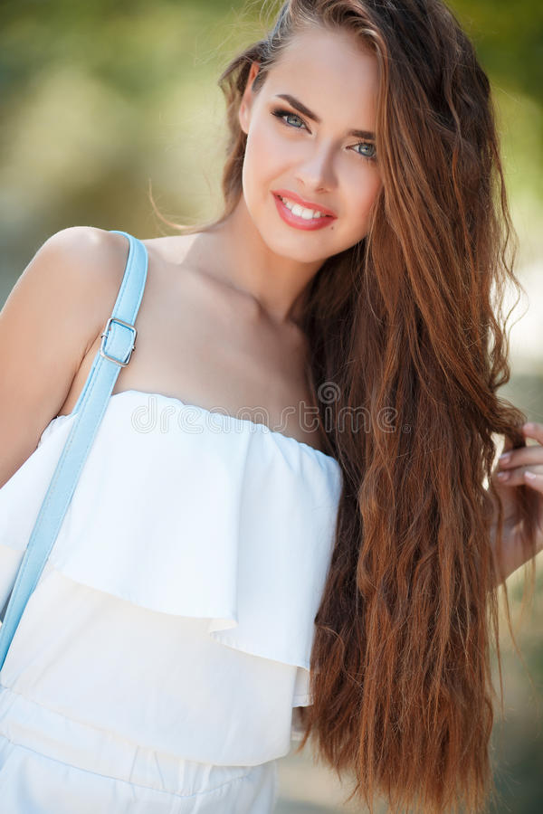 Portrait of beautiful woman in summer Park. Young beautiful brunette woman with long wavy hair and gray eyes,light makeup,pink lipstick dressed in a white blouse stock images