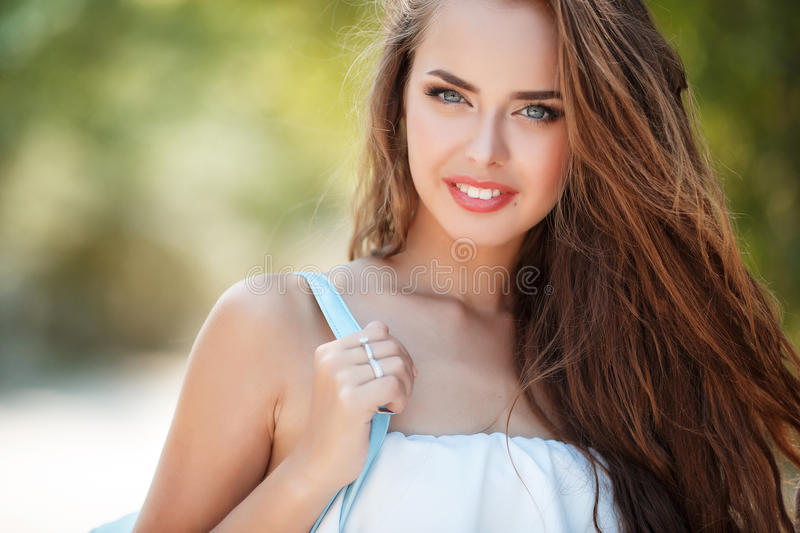 Portrait of beautiful woman in summer Park. Young beautiful brunette woman with long wavy hair and gray eyes,light makeup,pink lipstick dressed in a white blouse royalty free stock photos