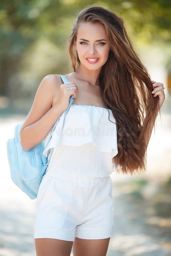 Portrait of beautiful woman in summer Park. Young beautiful brunette woman with long wavy hair and gray eyes,light makeup,pink lipstick dressed in a white blouse stock photography