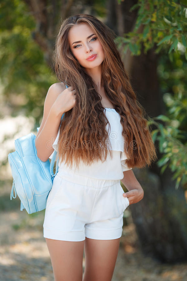 Portrait of beautiful woman in summer Park. Young beautiful brunette woman with long wavy hair and gray eyes,light makeup,pink lipstick dressed in a white blouse royalty free stock photography
