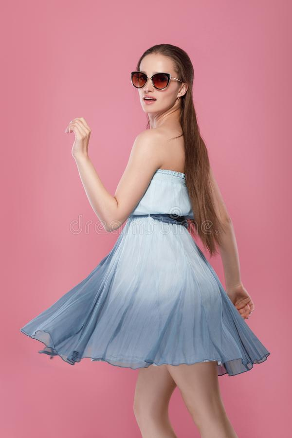 Woman in sunglasses and blue dress stock photo