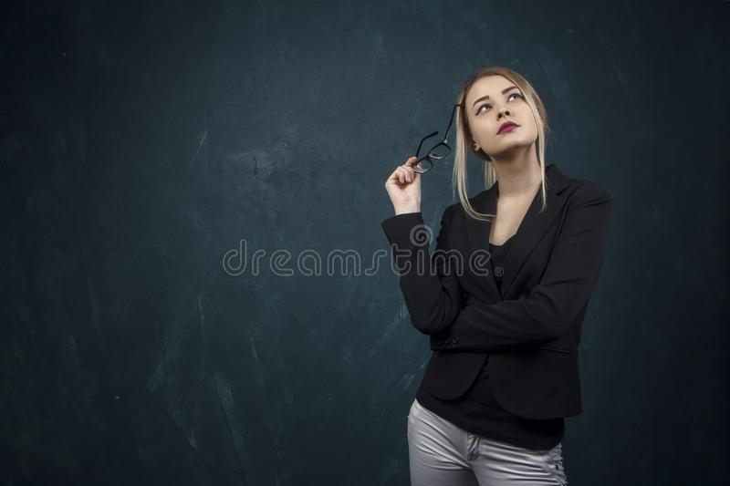 Portrait of a beautiful woman with sunglasses in hands and suit against a blue textural wall with place for text. stock photos