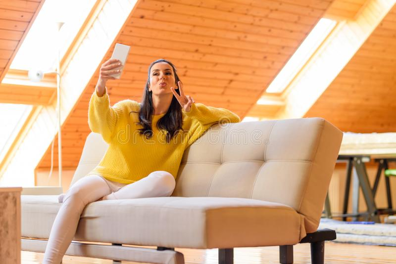 Portrait of a beautiful woman taking a selfie photo her the phon. E while relaxing on the sofa in a wooden attic loft.r royalty free stock photos