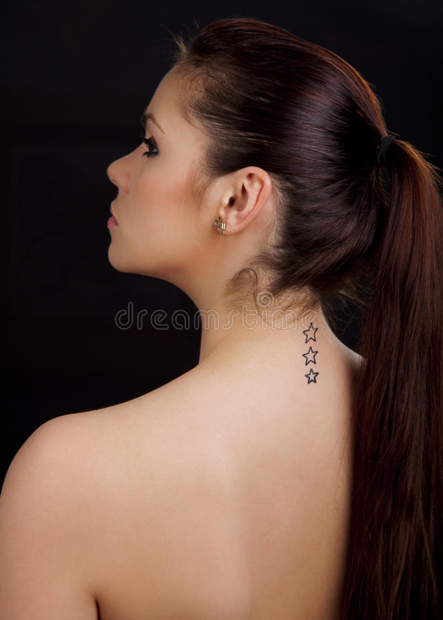 Portrait of a beautiful woman with tattoo on her back. Portrait of a beautiful young romanian woman with star shaped tattoos on her back wearing an earring stock photo
