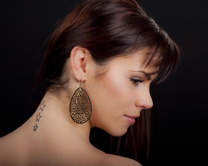 Portrait of a beautiful woman with tattoo on her back. Portrait of a beautiful young romanian woman with star shaped tattoos on her back wearing an earring and stock images