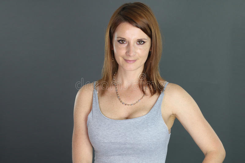 Portrait of a beautiful woman of thirty years. Over a gray background stock photography