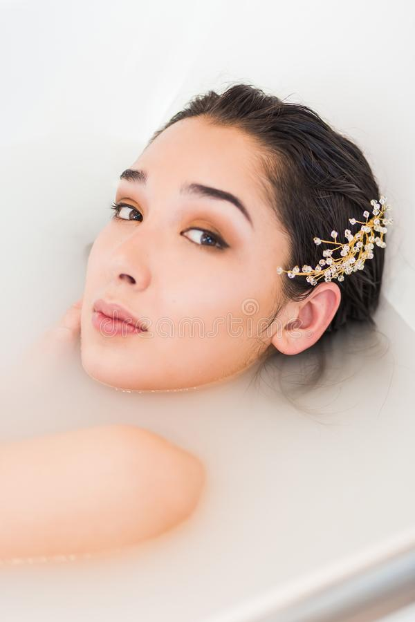 Portrait of a beautiful woman in the water. wellness treatment in bath. With milk royalty free stock images