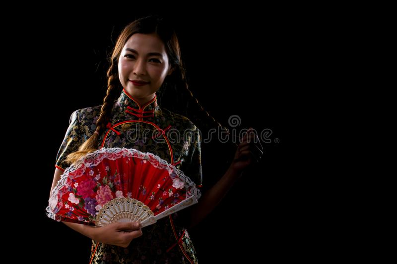 A beautiful woman is wearing chinese cloth and holding red folding fan stock photo