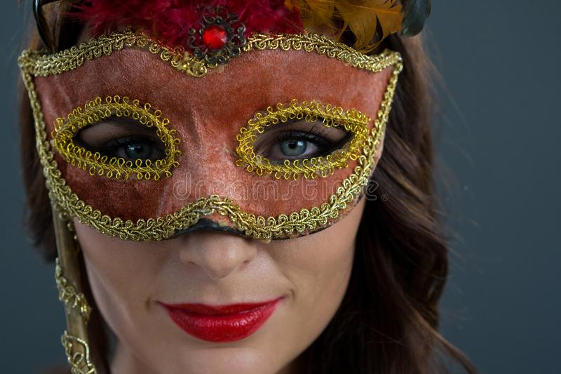 Woman wearing masquerade mask against black background royalty free stock images