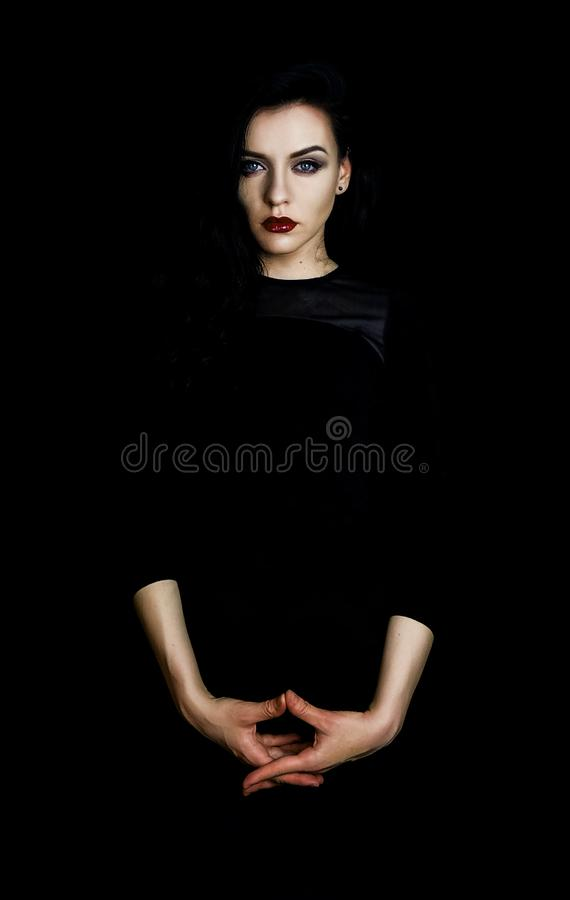 Portrait of a beautiful woman wearing red lipstick and an all black outfit, black background. Portrait of a beautiful woman wearing an all black outfit. Fierce stock photo