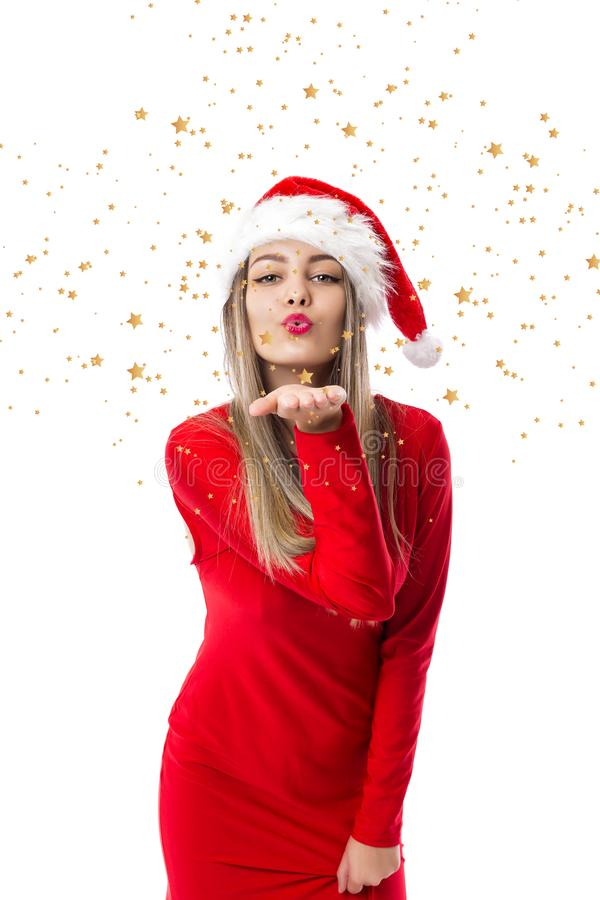 Portrait of beautiful woman wearing santa hat and blowing stars royalty free stock images