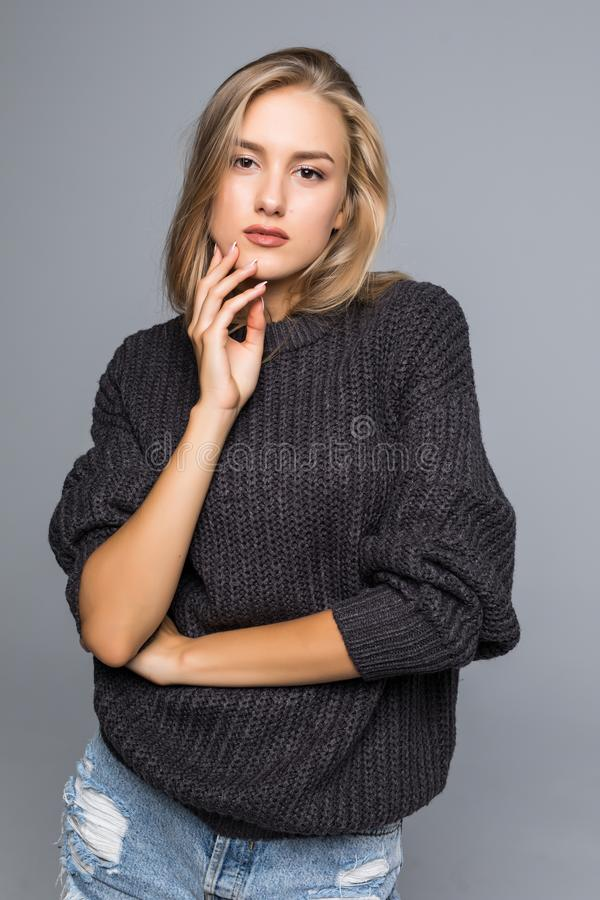 Portrait of a Beautiful Woman wearing a Warm knit Sweater on a gray background isolated stock images