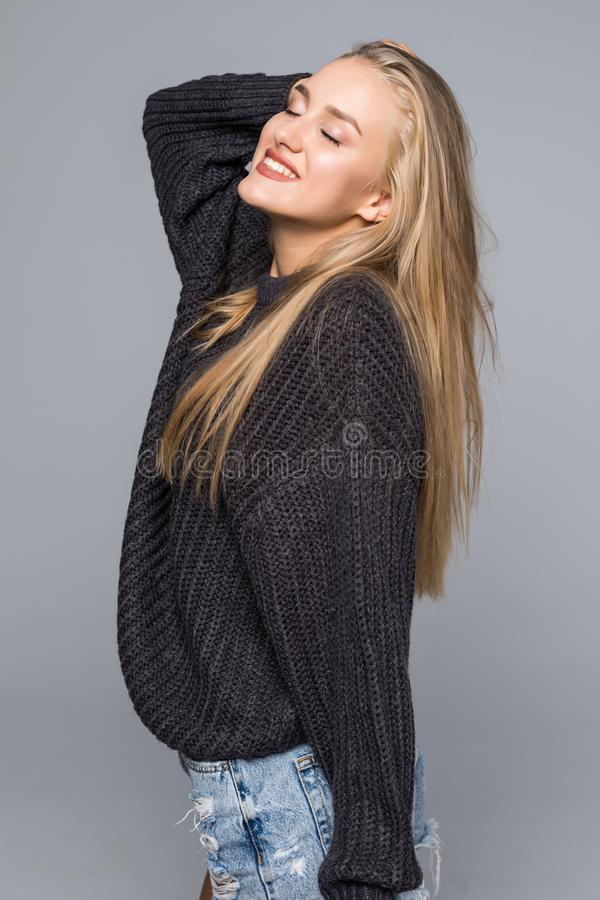 Portrait of a Beautiful Woman wearing a Warm knit Sweater on a gray background isolated stock photos