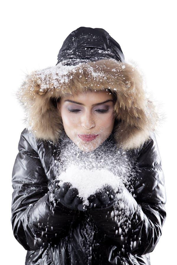 Beautiful woman blowing snow on studio royalty free stock photo