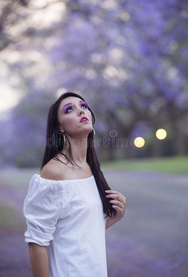 Portrait of beautiful woman in white dress standing in street surrounded by purple Jacaranda trees royalty free stock images