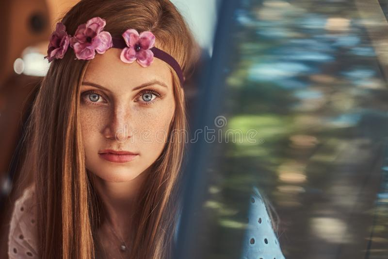 Portrait of a beautiful woman in a white dress and white wreath on the head, sitting in the car in the back seat. stock photo