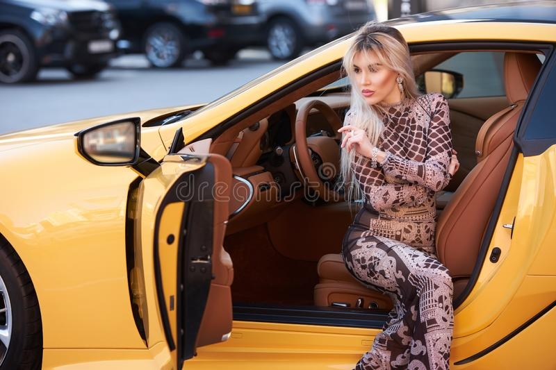 Portrait of a beautiful woman with yellow sports car outdoor, close-up. Portrait of a beautiful woman with yellow sports car outdoor. Business Woman posing in stock images