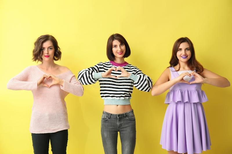 Portrait of beautiful women making hearts with their hands on color background royalty free stock photo