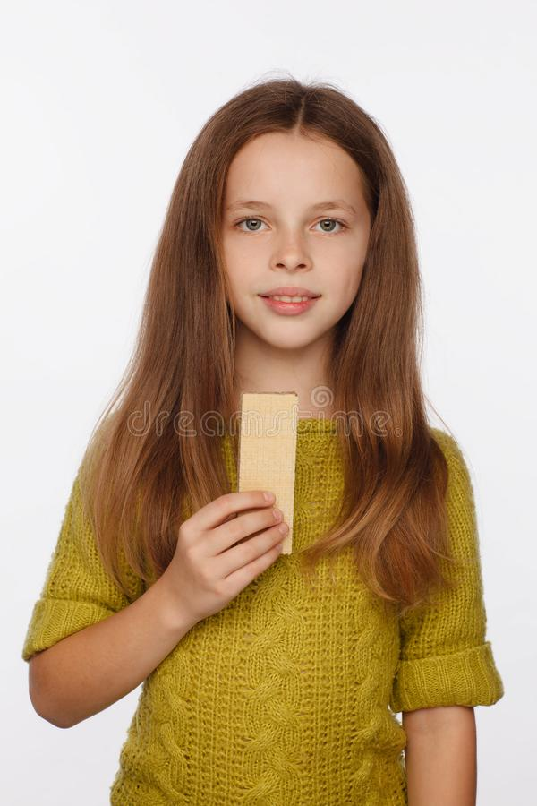 Portrait of a beautiful 8 year old girl in a sweater and with a wafer in her hand. White background stock images