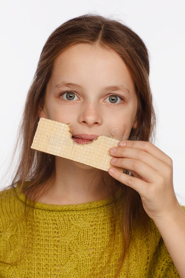 Portrait of a beautiful 8 year old girl in a sweater and with a wafer in her hand. White background royalty free stock photo