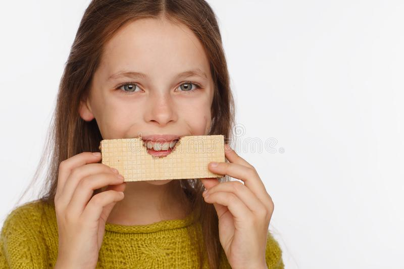 Portrait of a beautiful 8 year old girl in a sweater and with a wafer in her hands. White background royalty free stock images